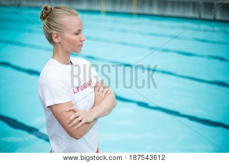 Confident female lifeguard standing at poolside