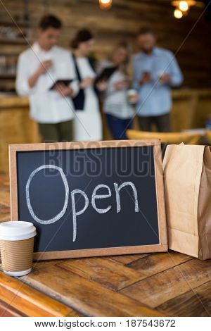 Open signboard with disposable coffee cup and paper bag on table in cafeteria