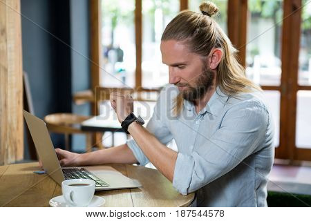 Young man checking time while sitting at table in coffee shop