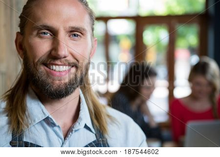 Portrait of confident male barista with female customers in background at coffee shop