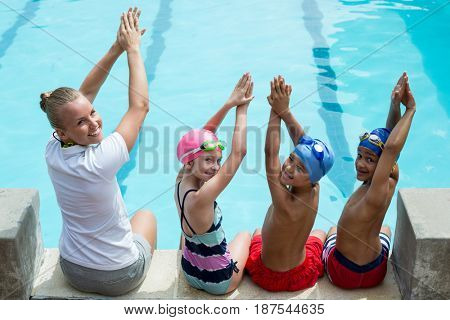 Portrait of swimming instructor with students at pool side
