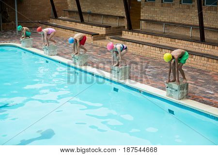 Swimmers preparing to dive off from starting block at poolside
