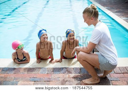 Side view of female swimming trainer teaching students at pool side
