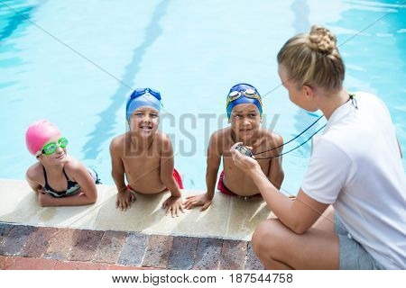 High angle view of female swimming trainer teaching students at pool side
