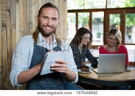 Portrait of happy male barista writing orders with female customers in background at coffee shop