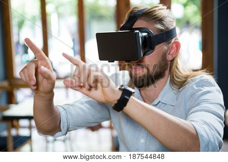 Young man wearing virtual glasses in coffee shop