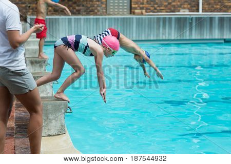 Mid section of female instructor monitoring time of children diving in pool