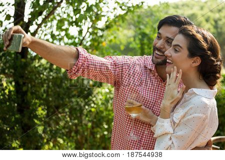 Happy couple taking selfie through smart phone at park