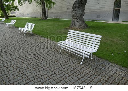 Line Of Empty White Benches In The Park
