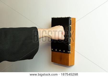 Martial Arts Master Punching A Japanese Traditional Makiwara Wood Board Wearing A Black Gi