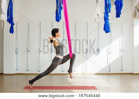 Adult woman practices inversion anti-gravity yoga position in studio. Girl stretches leg with help of hammock in gym, aerial yoga concept