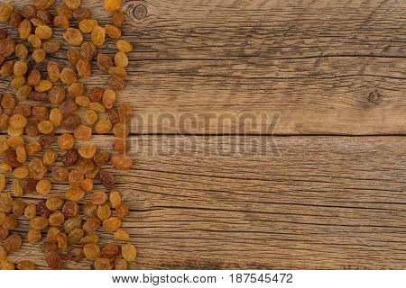 Raisins on the old wooden table. Top view.