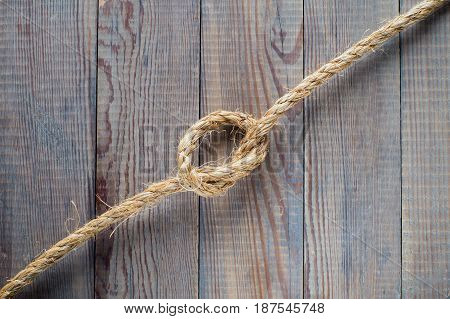 Knot of the rope on the wooden background. Rope with knot on blank antique brown rustic wood background with copy space.