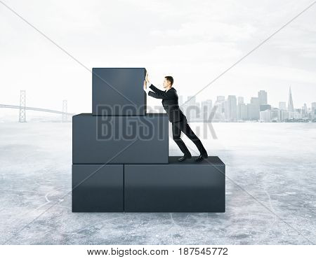 Businessman pushing abstract grey blocks on city background. Difficulty concept. 3D Rendering