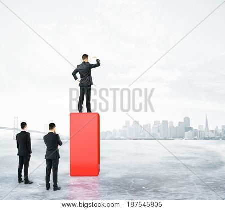 Businessman standing on abstract red pedestal on city background and looking into the distance. Leadership concept