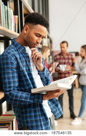 Image of young concentrated serious african man student standing in library reading book. Looking aside.