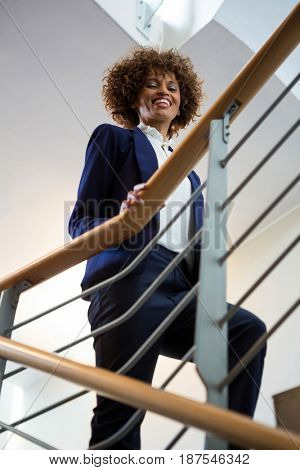 Portrait of businesswoman walking upstairs in the office