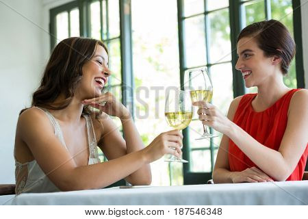 Smiling young woman toasting wine glasses in restaurant