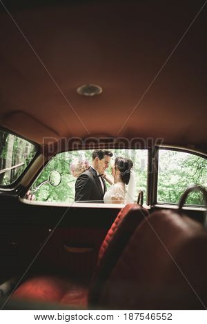 Stylish wedding couple, bride and groom kissing and hugging near retro car in autumn.