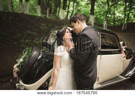 Beautiful wedding couple posing near splendid retro car.