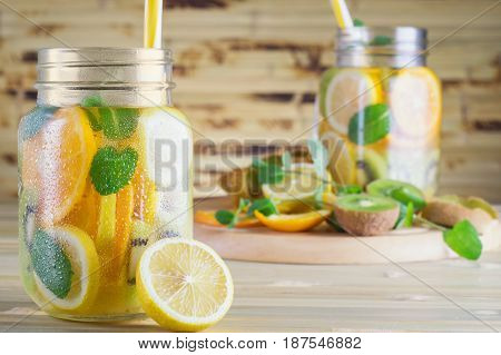Fresh lemonade with mint. Detox fruit water on wooden table. Summer refreshing citrus water in a mason jar on a bamboo table. Fruit cocktail with lemon orange kiwi.