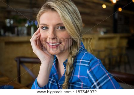 Portrait of smiling young woman with blond hair in coffee shop