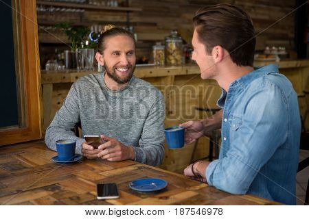 Smiling young man talking with friend at table in coffee shop