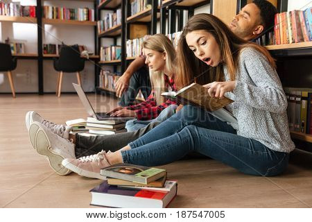 Image of young concentrated students sitting in library on floor using laptop computer and reading books. Looking aside.