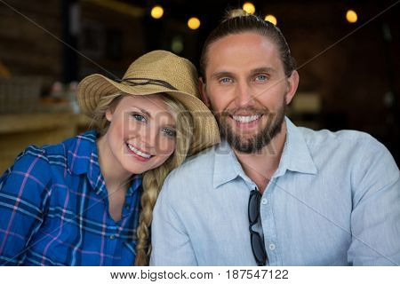 Portrait of loving young couple smiling in coffee shop