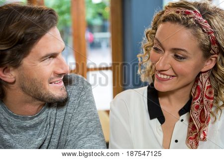 Smiling young couple looking at each other in coffee shop