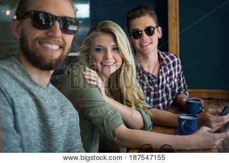 Portrait of happy male and female friends at table in cafe