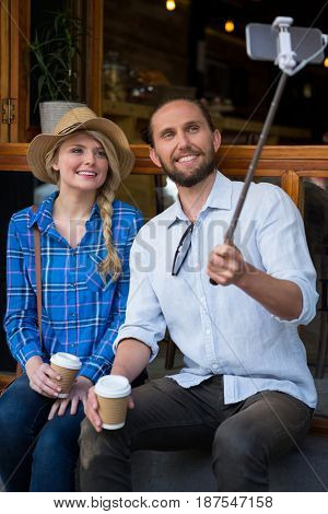 Smiling young couple photographing through selfie stick in coffee shop