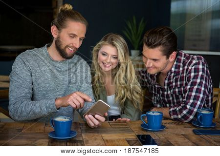 Young man showing smart phone to friends at table in coffee shop