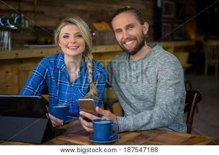 Portrait of smiling young couple with coffee and technologies in cafe