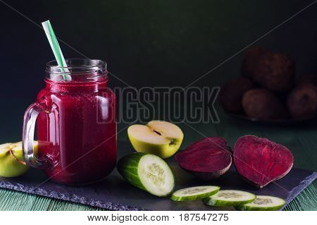 Beetroot smoothie in a mason jar with a straw and ingredients on a wooden background. Fresh beet juice detox. Organic antioxidant smoothies made of beet apple cucumber. Healthy vegan raw food.