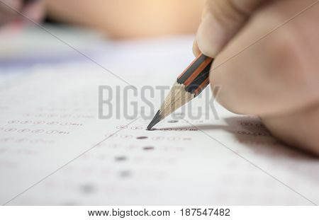 asian hands student testing in exercise exams answer sheets with color pencil in school