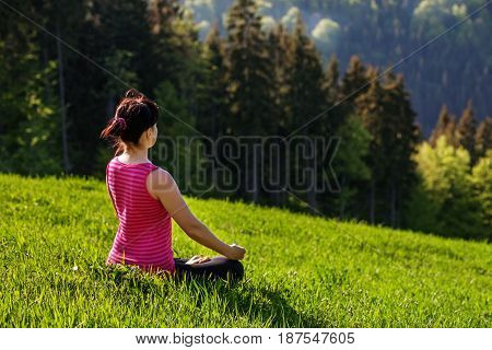 The young woman meditating in nature. Mountains. The concept of a healthy lifestyle travel and yoga.