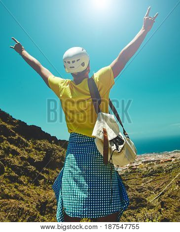 Young Happy Man In Stylish Clothes On Top Of The Mountain Reaches For The Sun