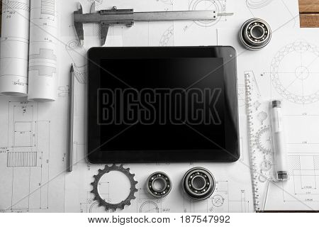 Engineering supplies, tablet and blueprints on workplace