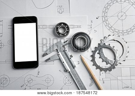 Engineering supplies, phone and blueprints on workplace