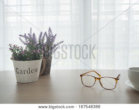 office table with beautiful variety flower on pot and modern eyeglasses white ceramic coffee cup on blurry beautiful white drape window texture background.