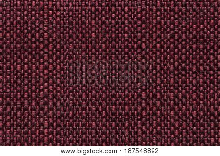Dark red background with checkered pattern closeup. Structure of the maroon fabric macro.