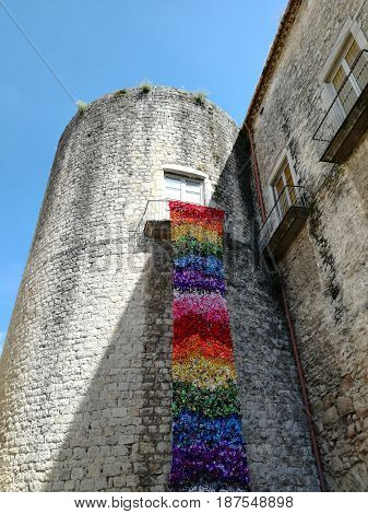 Medieval castle tower with balcony with colorful flower mantle on holiday