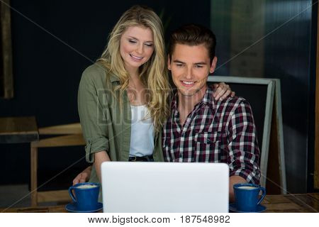 Smiling young couple using laptop at table in coffee shop