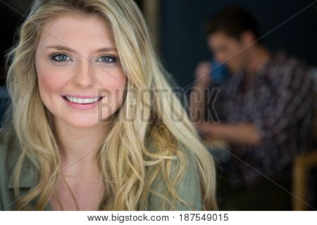 Portrait of beautiful young woman with blond hair in coffee shop