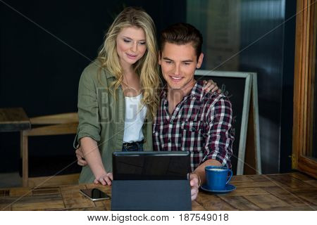 Smiling young couple using tablet PC at table in coffee shop