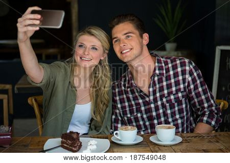 Smiling young couple taking selfie with cell phone in cafeteria