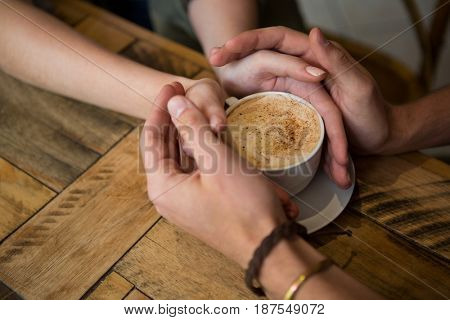 Close-up of couple holding hands and coffee cup in cafeteria