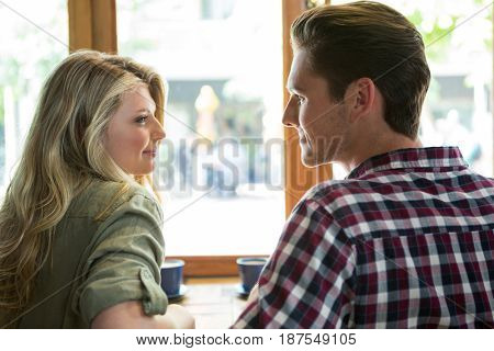 Loving young couple looking at each other in coffee house