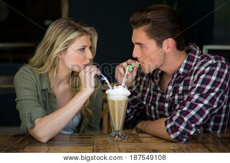Loving young couple having milkshake at table in coffee shop